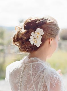 Hairstyle -- Love the understated elegance of the flower -- see the wedding here: http://www.StyleMePretty.com/2014/05/14/rustic-moose-head-ranch-wedding/ #SMP - Photography: CarriePattersonPhotography.com