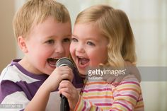 Stock Photo : Caucasian brother and sister singing into microphone