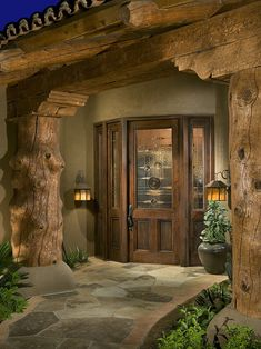 I love several elements of this entryway - the tree trunk pillars, the path and lights on either side, and the way the door is in a bow window shape.