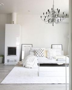 Rento valkoinen tyyli olohuoneen sisustuksessa. Moderni takka kruunaa kokonaisuuden.
