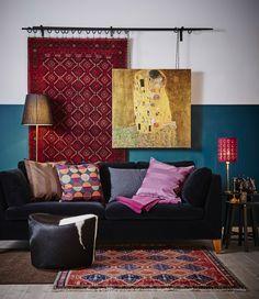 una habitación con un sofá, un cuadro y muchos textiles diferentes en colores coordinados.