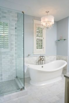 Ramos Design Build Corporation | my favorite bathroom, clean glass shower walls, subway tile (not too much), curved freestanding tub, pale blue walls, and a small chandelier for the bathroom
