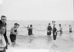 A group of men playing water baseball in the surf on July 24, 1914.