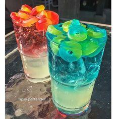 ELECTRIC BLUE TYPHOON (blue): Top Layer: 1 oz. UV Blue Vodka, 1/2 oz. Island Punch Pucker, 1 1/2 oz. Lemon Lime Soda. Bottom Layer: 1/2 oz. Simple Strup, 2 oz. Lemonade, 1/2 oz. Blueberry Lemonade Rum, and Lifesaver Gummies Collisions. SWEET COLLISION (red): Top Layer: 1 oz. UV Cherry Vodka, 1/2 oz. Strawberry Liqueur, 1 1/2 oz. Lemon Lime Soda. Bottom Layer: 1/2 oz. Simple Syrup, 2 oz. Lemonade, 1/2 oz. Blueberry Lemonade Rum, and Lifesavers Gummies Collisions.