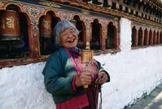 An old woman with prayer wheels laughing at the Kyichu Buddhist Temple in Paro, Bhutan - robertharding/REX Shutterstock