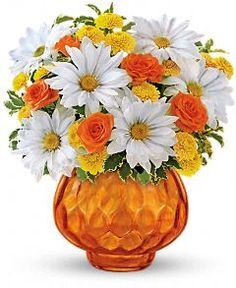 The cheerful bouquet includes orange spray roses, white daisy spray chrysanthemums and yellow button spray chrysanthemums accented with fresh greenery.