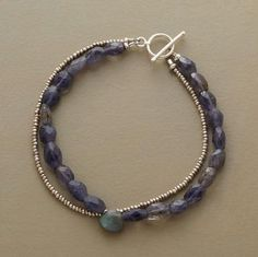"""Tandem trails of denim blue iolites and sterling silver seed beads begin and end at a toggle clasp. Front and center is a faceted labradorite. Exclusive. Handmade in USA. Approx. 7-1/2""""L."""