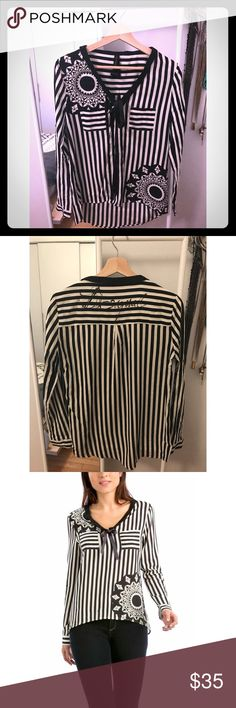 Desigual Black and White Striped Blouse Black and white stripes blouse with black ribbon tie in the front. Black flower pattern through out and front pockets on the chest area. Falls slightly longer in the back than in the front. It is a European Medium so runs slightly small around the arms. Desigual Tops Blouses