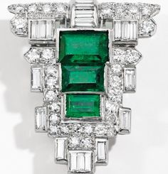 14 KARAT WHITE GOLD, EMERALD AND DIAMOND CLIP-BRACELET COMBINATION, TRABERT & HOEFFER - MAUBOUSSIN The flexible white gold strap composed of rectangular links decorated with a shield-shaped clip set with emerald-cut emeralds weighing approximately 2.75 carats, accented by baguette and old European-cut diamonds weighing approximately 3.00 carats, length adjusts from 6½ to 7¼ inches, bracelet signed T&HM, numbered 1127; clip is detachable, unsigned; circa 1940.