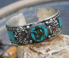 Ohm' Armband gemaakt van Tibetaans zilver met een 'Ohm' symbool van Koper en prachtige versieringen van Turkoois stukjes aan beide zijden.  Breedte 2.3 cm   De armband is instelbaar door de open achterkant.  Handgemaakt en afkomstig uit Nepal.  Tibetaans zilver bestaat uit zilver en andere metalen, waaronder koper.   Tibetaans zilver is prachtig, het blijft betaalbaar en het is makkelijk in het onderhoud.