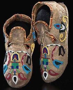 Crow beaded hide moccasins, thread- and sinew-sewn and beaded using greasy yellow, light blue, cobalt, red white-heart. white, and pink; with outlined florals and geometrics on vamps and cuffs; cuffs edged in yellow and red cotton, fourth quarter 19th century.