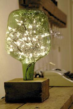 Lampara de damajuana con soporte de madera y luces como las de arbol de navidad dentro: