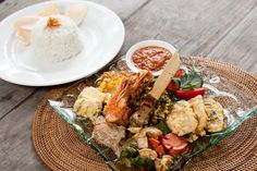 Nasi Campur ala Semar  Featuring simple example of Indonesian dishes consist of; sate Lilit, pepes ikan, ayam goreng kecap, tempe, prawn tempura, sayur plecing, sambal, served with steamed rice.