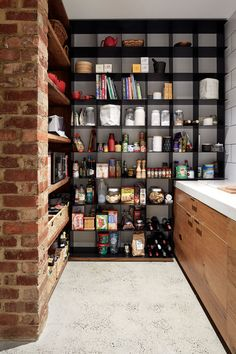 This modern pantry has open black steel shelving and polished concrete floors. I love the idea.