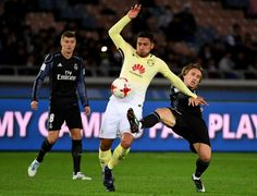 Club America's defender Bruno Valdez (C) fights for the ball with Real Madrid's midfielder Luka Modric (R) during the Club World Cup semi-final football match between Mexico's Club America and Spain's Real Madrid at Yokohama International stadium in Yokohama on December 15, 2016. / AFP / TOSHIFUMI KITAMURA