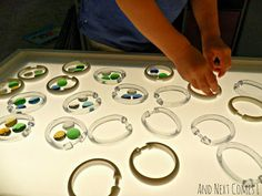 Shower Curtain Rings and Glass Stones on the Light Table from And Next Comes L ... maybe I'll make my kids a light table for christmas...