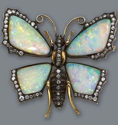 An opal and diamond brooch in the form of a butterfly, with articulated opal wings and body set with old European-cut diamonds; mounted in eighteen karat gold; length: 1 3/4in.