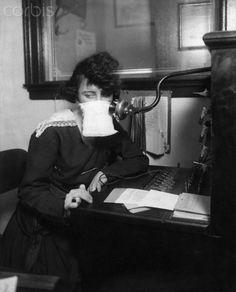 Original caption: Flu epidemic, 1918: Telephone operator with protective gauze.
