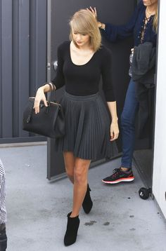 Known for her inhuman ability to look *perfect* post-workout sesh, it's not all too surprising that Swift looks like a million bucks exiting the gym in Los Angeles. Carrying her favorite new Prada bag (next slide), the singer keeps it simple and chic in a black fitted top, gray skater skirt and heeled booties.