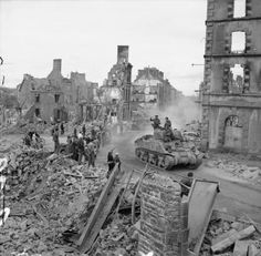 A Sherman tank drives through the remains of Flers, 17 August 1944.