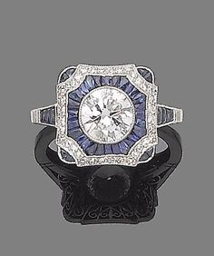 A sapphire and diamond dress ring. The square plaque centrally-set with a brilliant-cut diamond, within a calibré-cut sapphire surround, between single-cut diamond borders, to tapering similarly-cut sapphire shoulders, millegrain-set throughout, principal diamond approx. 1.15cts. Art Deco or Art Deco style.