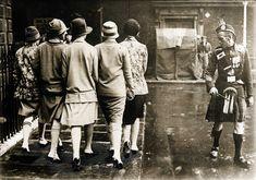 De nieuwste mode in Engeland zijn kousen voor dames, zoals de Schotse Highlanders/ Hooglanders dragen, Engeland 1927. Foto: Vijf dames met lange kousen aan, worden bij het voorbijgaan bekeken door een Schot in klederdracht.