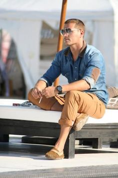 Shop this look on Lookastic:  https://lookastic.com/men/looks/denim-shirt-chinos-loafers-sunglasses-watch/11880  — Grey Sunglasses  — Blue Denim Shirt  — Black Rubber Watch  — Khaki Chinos  — Tan Suede Loafers