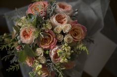 Bridal bouquet in coral Miss Piggy roses, peach Sweet Juliet David Austin roses, cream stocks and astilbe, creamy peach spray roses, silvery blue eucalyptus and dusty miller foliage. Elegant, soft and natural.