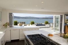 how awesome! open up walls and windows!  Kitchen water view folding sliding doors