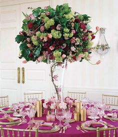 Roses, viburnum, and snapdragons fill a grapevine- and orchid-lined vase.