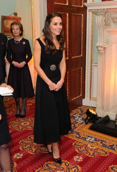 The Duchess wore a black cocktail dress by Preen with a bejewelled belt and vertiginous black Prada heels in London tonight