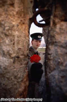 An East German border guard offers a flower through a gap in the Berlin Wall on the morning it fell, 1989.