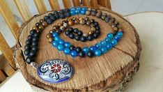 This mala necklace is made of 99 pieces; includes 3 different type of natural gemstones. 8 mm blue jade 8 mm obsidian 8 mm frosted tiger eye stone. We can design it as a 108 beads mala necklace. ABOUT Jewelry Designer of Emotional Dreams offers an exciting collection, designed and
