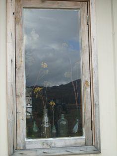 Botellas, flores y nubes en la ventana.