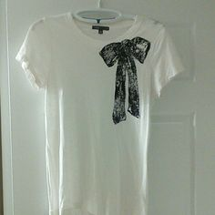 J. Crew velvet textured bow t-shirt Cream colored short sleeved shirt from J. Crew. Features a large velvet bow in the upper left corner in navy. Worn only a handful of times. J. Crew Tops Tees - Short Sleeve