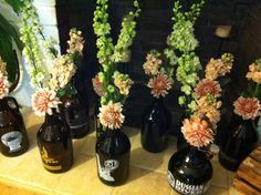 Beer growlers as centerpiece/table assignments. Great way to have a masculine touch, but with the soft colors the flowers make it romantic. Angels Petals.