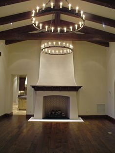 Amazing Chandelier and exposed wood beams. I want to curl up on a couch in front of that fireplace looking at that ceiling. Perfect.