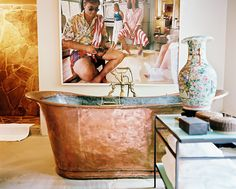 This Vicente Wolf–designed bathroom features a large-scale retro photograph hung above a hammered copper freestanding tub. The space lends itself to a casual yet enviable dolce vita.