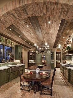 Luxury kitchen with arched brick ceiling and long center island with an attached cozy table for two.