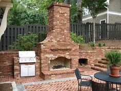 An Outdoor Fireplace with built in grill and wood storage.