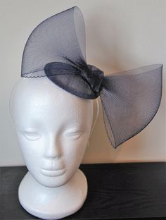 This is a pretty handmade fascinator in navy with a large crinoline bow. It comes on a navy sinamay base and an ivory hairband.  This item would be perfect for a wedding, party or the races!  Please allow 2 weeks for me to make this and 2 - 3 working days for postage (if based in UK). Otherwise, please allow 5 - 7 working days for postage.