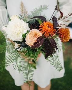 The maid of honor and bridesmaid carried smaller bouquets of dahlias, umbrella ferns, geranium foliage, caramel Antike garden roses, ranunculus, thistle, sea grass, and plum foliage.