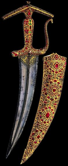 Indian (Mughal) kanjhar (curved dagger). Circa 1615-1620,  this dagger and scabbard, thought to have been commissioned and designed by Emperor Jahangir around 1619, is set with rubies, unpolished diamonds, emeralds,  transparent emerald-green glass, blue glass, ivory and layered agates