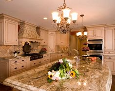 Granite kitchen island with chandelier work lighting as part of this Faralli Kitchen remodel.