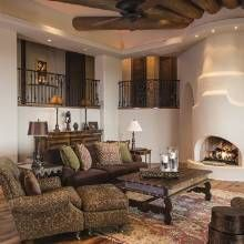 Indoor balconies and a kiva style fireplace make for a cozy sitting area