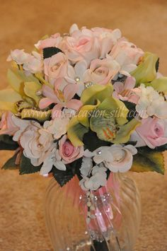 Green orchids, pink roses, and white stephanotis compose this dainty and romantic bridesmaid bouquet.