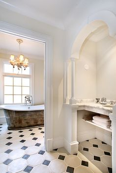 Beautiful Bathroom...love the tub and the black & white flooring, etc....