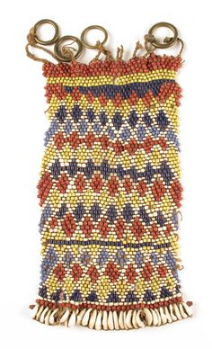 A Cameroon beadwork and cowrie shell rectangular cache sex, with four brass rings, 6in (15.2cm) wide.