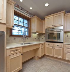 Nice kitchen redesign with under cabinet lights, removable cabinet fronts, raised dishwasher off the floor, lower and upper cabinets have accessible shelving and island has a separate lower counter top.   Love This!!