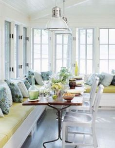 Eat in Kitchen with banquette seating with lime green cushions, a long wood table, metal chairs, pendant lights, paitned wood floor, and white casement windows